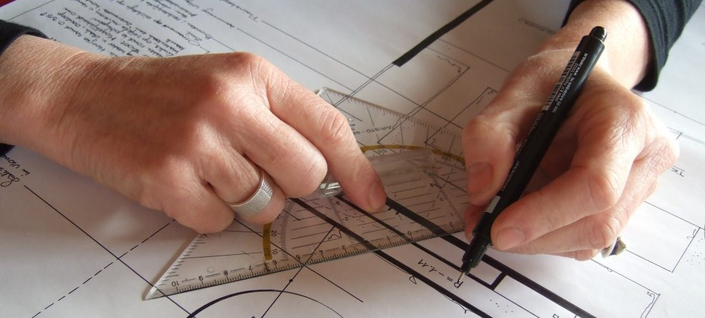 met pen en geodriehoek wordt een tuinontwerp getekend