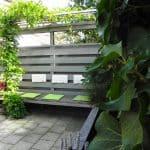 De tuin is klein maar dit hoekje is fijn om te zitten op de bank met het RVS pergoladak begroeid met blauwe regen.