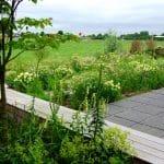 het terras in de achtertuin is omgeven door natuurlijk ogende borders. op de lange houten bank kun je zitten of liggen.
