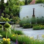 Terras van gegoten en geschuurd beton afgewisseld met grind. Het terras is omgeven door beplanting