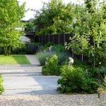 Achterste deel van de pijpenla tuin met grind, gegoten beton, gazon en borders