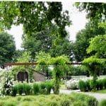 De gebogen cortenstaal pergola, grassenhagen en rozenborders omgeven cirkelvormig de stilte en meditatiekapel.