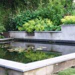 Een ca. 20cm verhoogde vijver met een keerwand aan de achterzijde waar water over een kleine waterval in de vijver stroomt.
