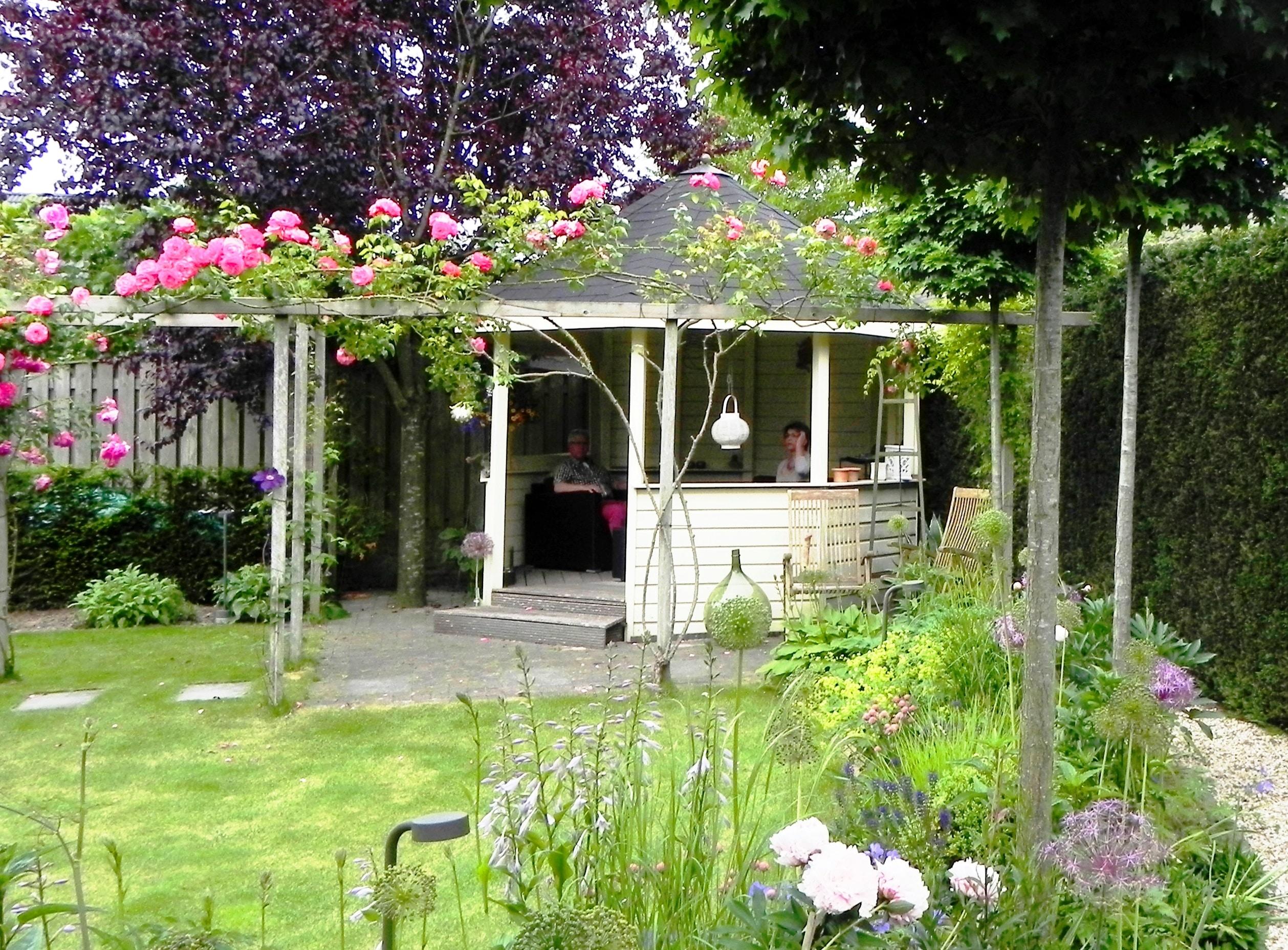 Een romantisch tuinhuisje en een met rozen begroeide pergola in een zonnige achtertuin.
