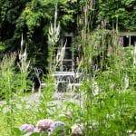 Een heel romantisch beeld met Hortensia's en hoge ijle planten en een klassiek wit tuinstel bij de gevel