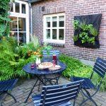 gezellig terrasje met donkerblauw meubilair omgeven door groene beplanting