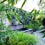 gemetselde vijverbak met hardstenen rand en beplanting van siergrassen en bamboe