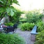 intieme groene tuin met bamboe, gemetselde waterbak, pergola, siergrassen en een vijgenboom