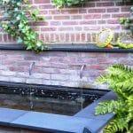 gemetselde verhoogde waterbak met hardstenen rand en twee gebogen metalen water uitlopen.