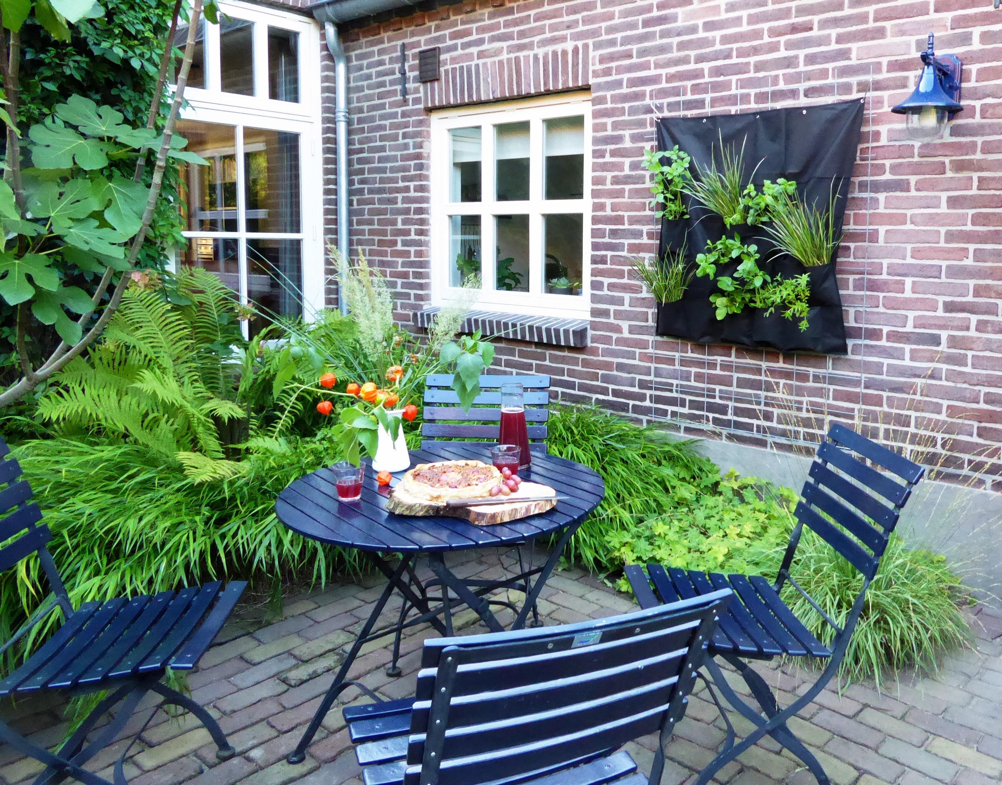 blauw tuinstel op een terras omgeven door groene planten