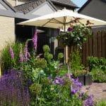 Parasol zorgt voor schaduw in de zonnige achtertuin met haar uitbundig bloeiende borders