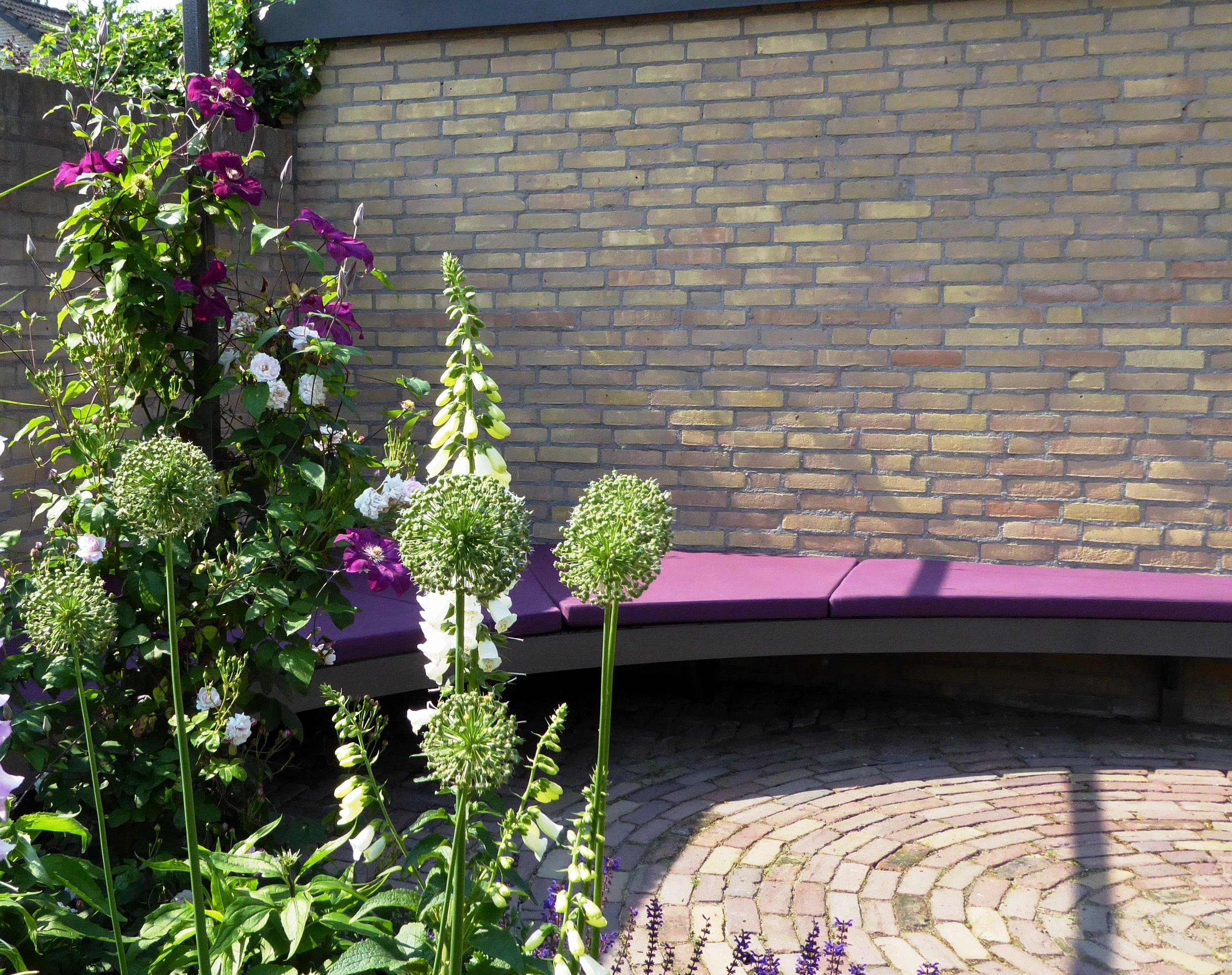 hoekbank tegen een muur met paarse kussen in de kleur van de beplanting
